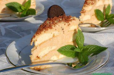torcik z kremem kajmakowym bez pieczenia przekładany biszkoptami, posypany czekoladą i ozdobiony ciasteczkami oreo